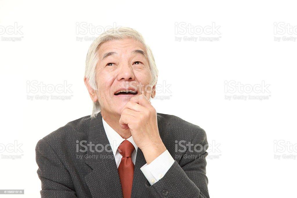 senior Japanese businessman dreaming at his future stock photo