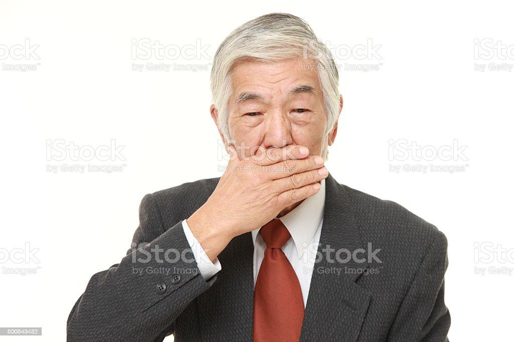 senior Japanese businessman making the speak no evil gesture stock photo