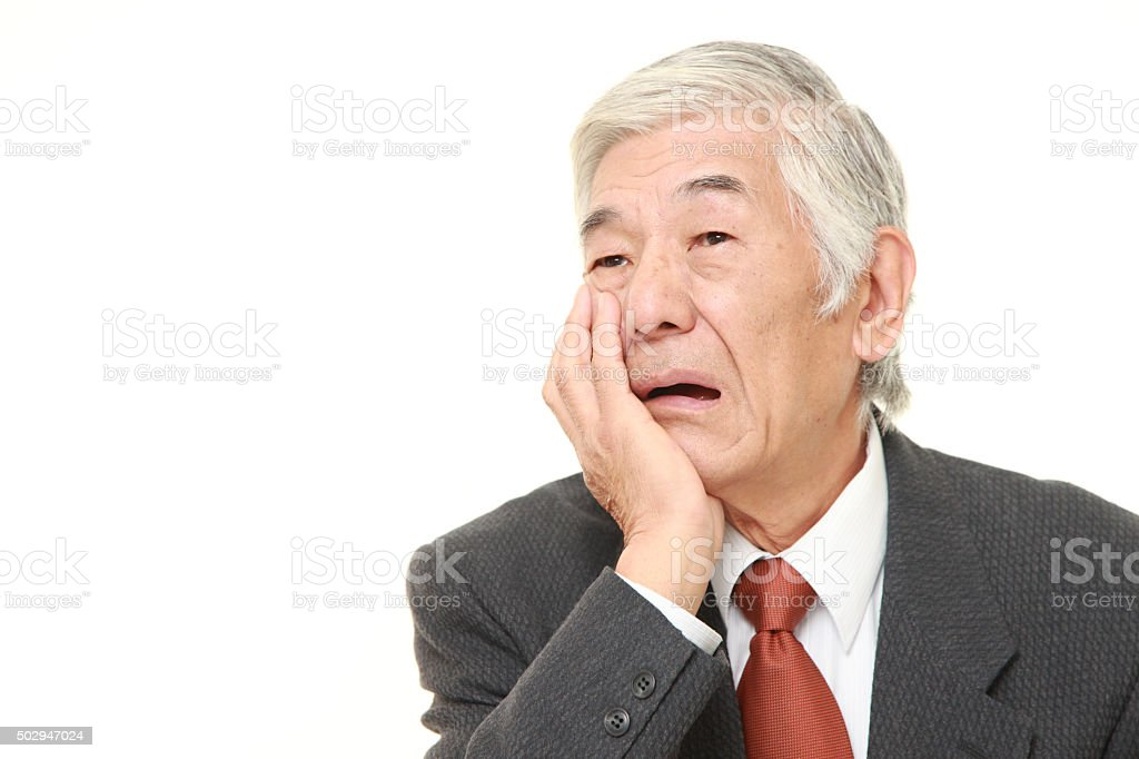 senior Japanese businessman suffers from toothache stock photo
