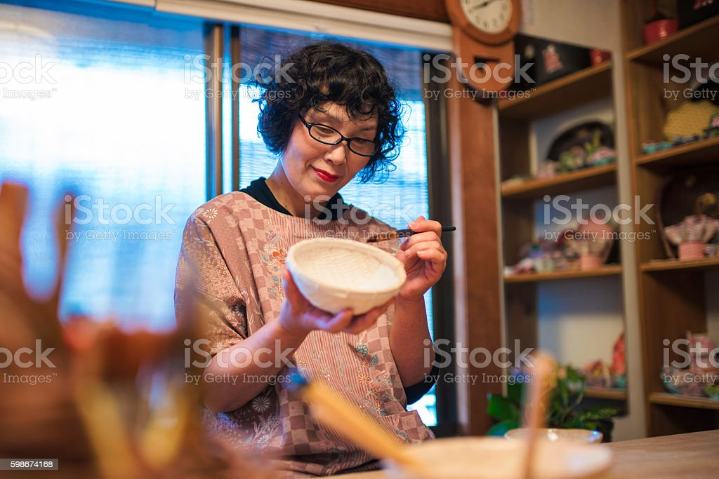 Senior Japanese Craftsperson painting a paper bowl stock photo