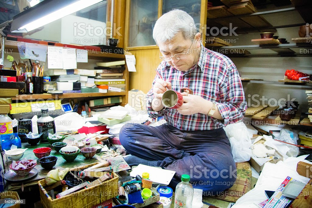 Senior Japanese male lacquer wood artisan painting a cup stock photo