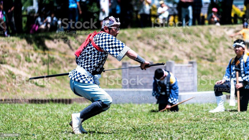 Senior Japanese man getting katana sword from it's case stock photo