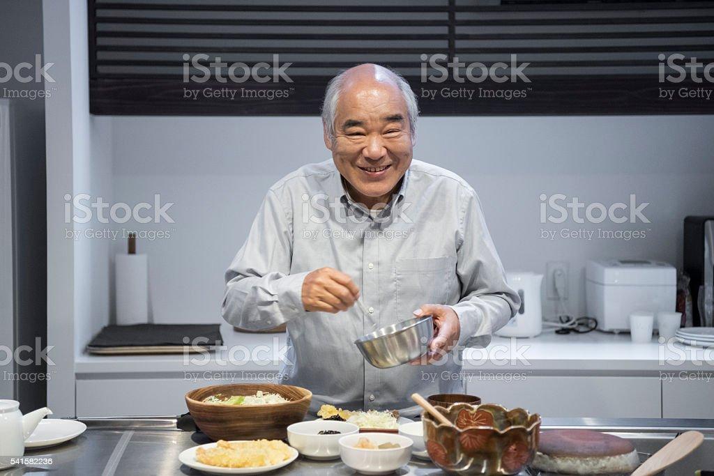 Senior Japanese man making dinner in kitchen, smiling stock photo
