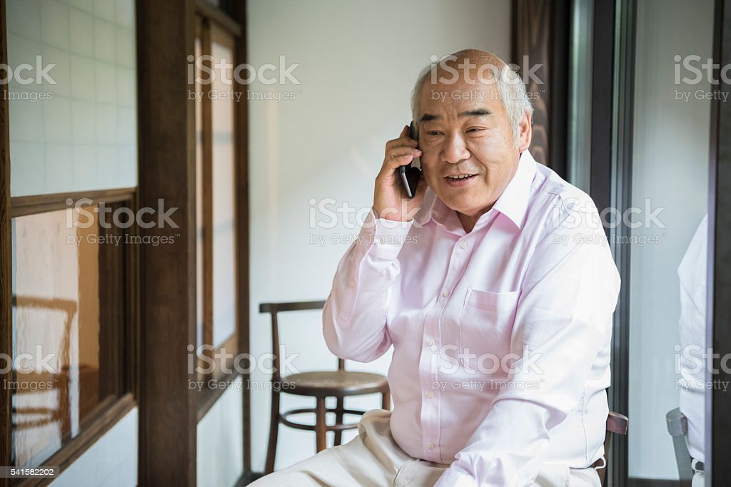 Senior Japanese man on telephone stock photo