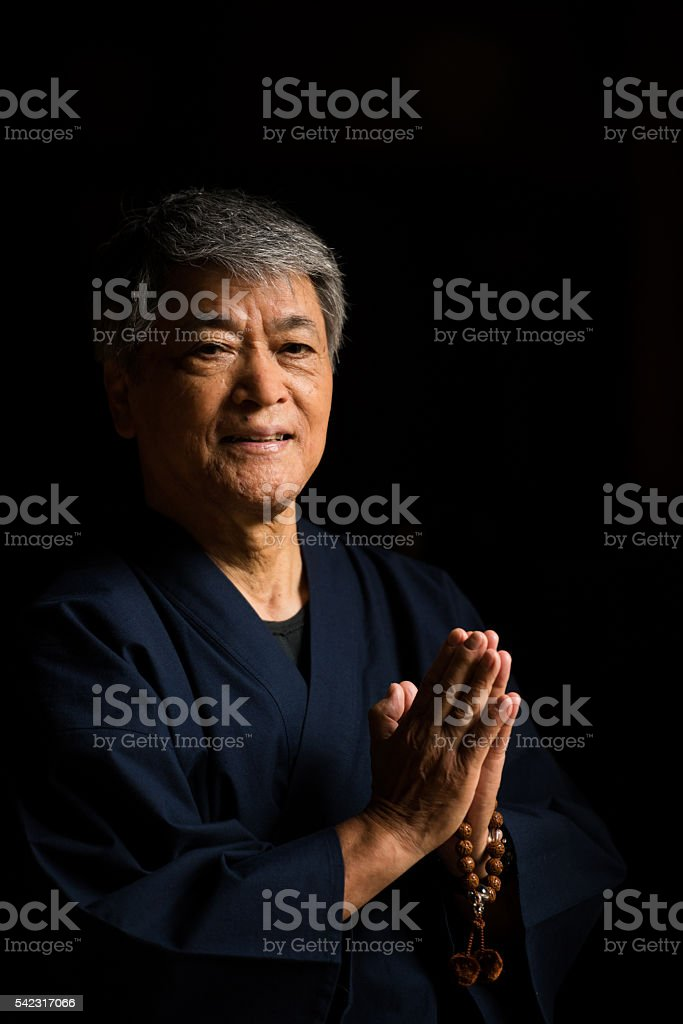 Senior Japanese man praying at a temple stock photo