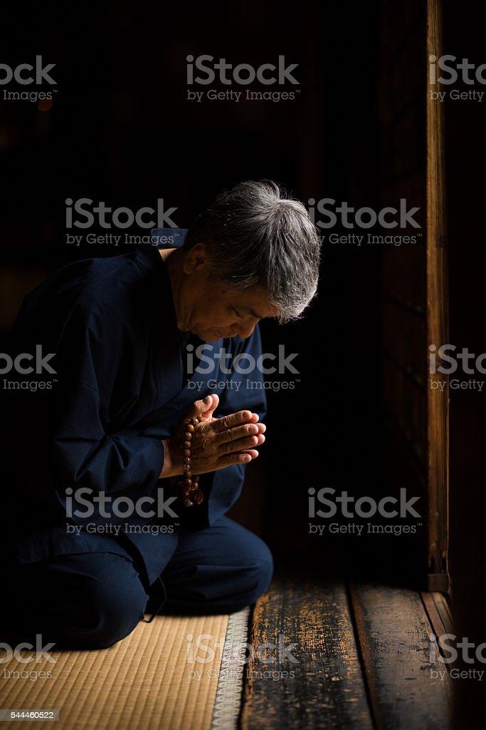 Senior Japanese man praying at a temple stock photo