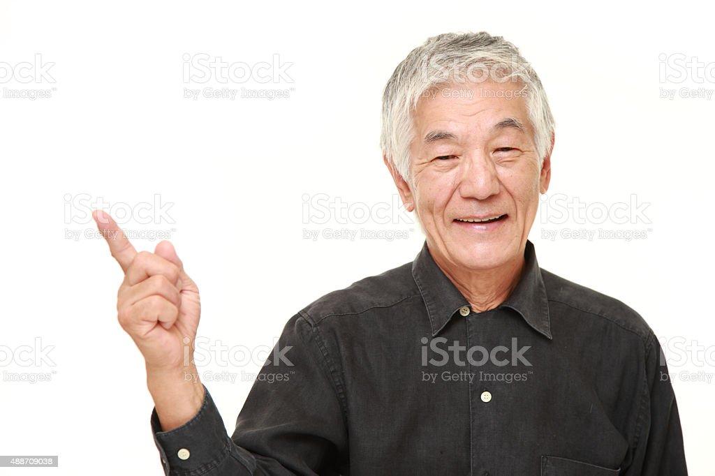 senior Japanese man presenting and showing something stock photo