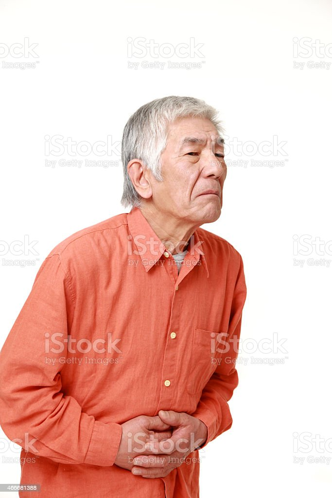 senior Japanese man suffers from stomachache stock photo