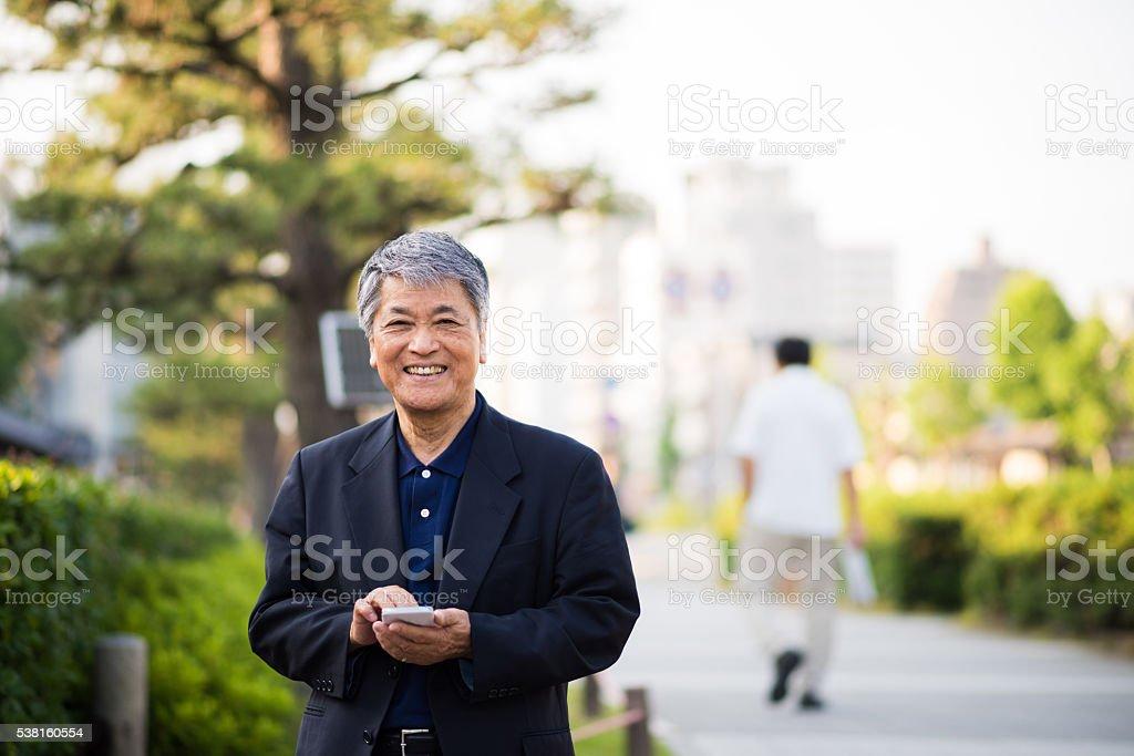 Senior Japanese man using a smart phone stock photo