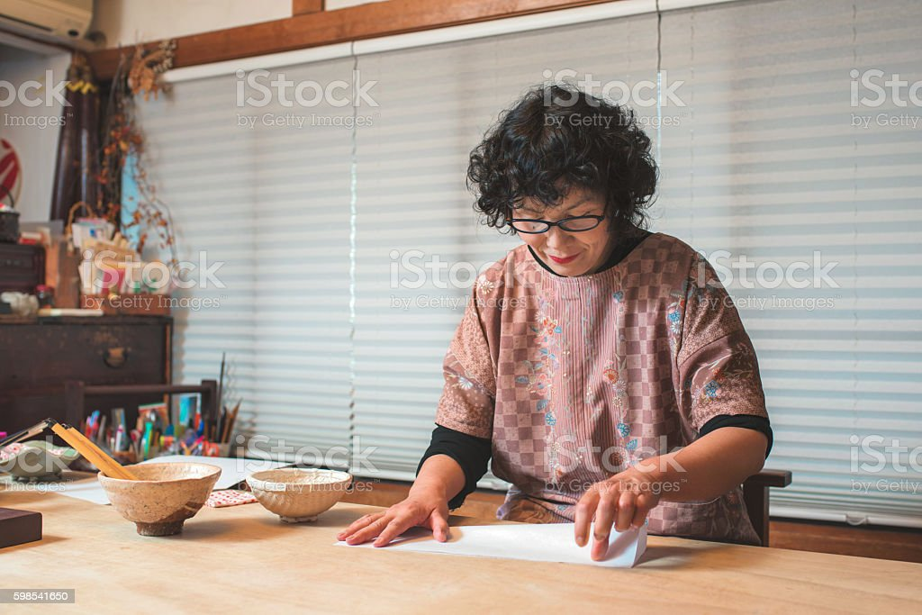 A Traditional Japanese craftswoman holding a sheet of paper in...