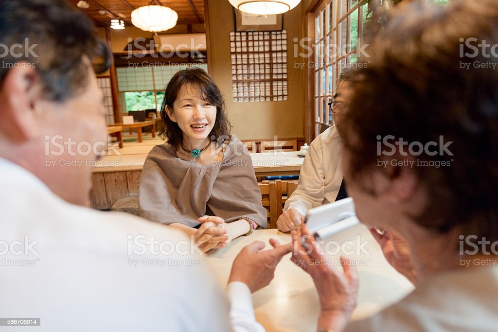 Senior Japanese Woman Shares Photos with Friends in Kyoto Restaurant stock photo