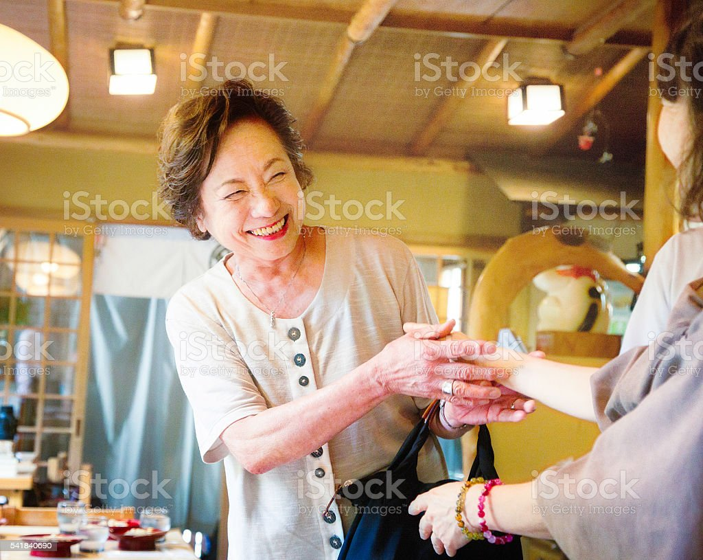 Senior Japanese woman smiles as she is greeted by friend stock photo