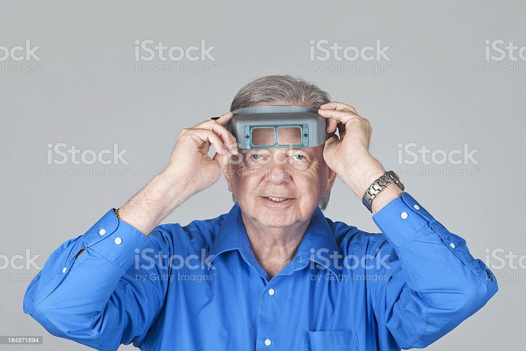 Senior Jeweler wearing magnifier goggles stock photo
