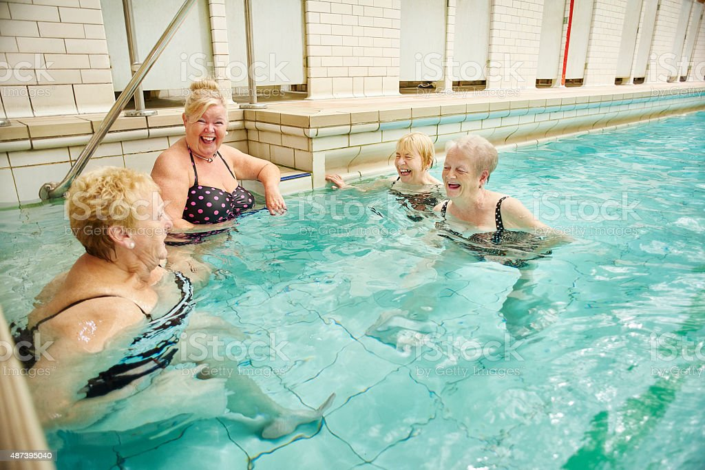 senior ladies gossip in pool stock photo