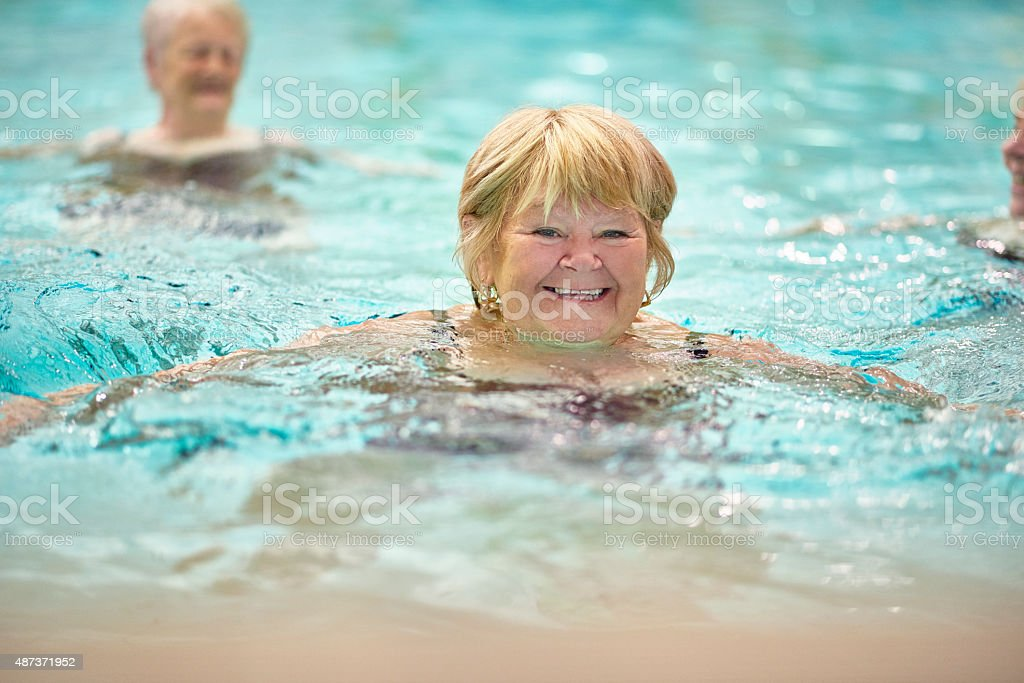 senior ladies having fun in pool stock photo