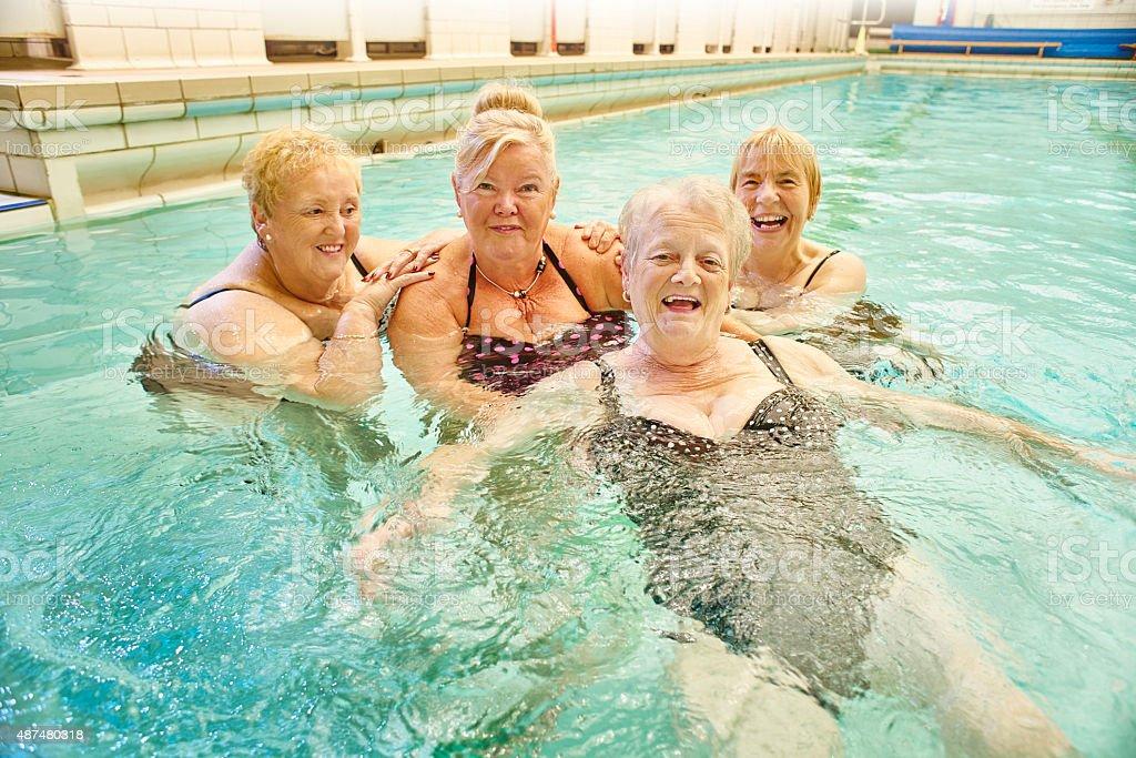 senior ladies smile to camera in pool stock photo