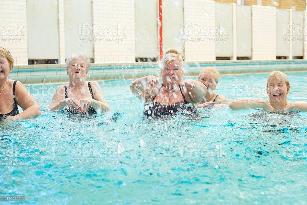 senior ladies splashing in pool stock photo