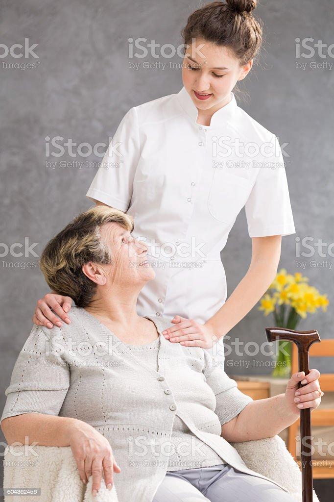 Senior lady and helpful caregiver stock photo