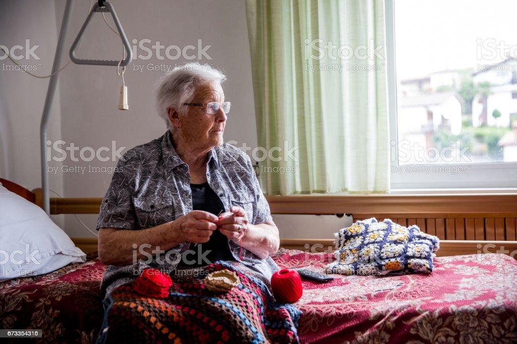 Senior Lady Crocheting in Her Room in Retire Community stock photo