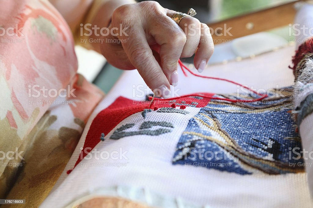 senior lady embroiders a tapestry royalty-free stock photo