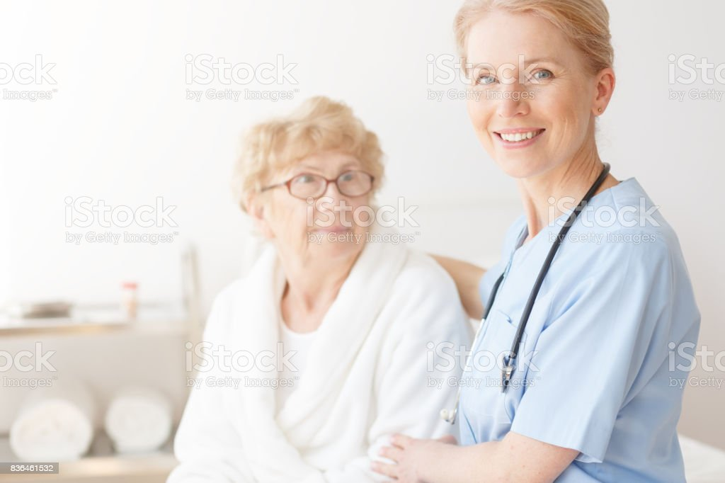 Smiling nurse in blue uniform with stethoscope caring about senior...