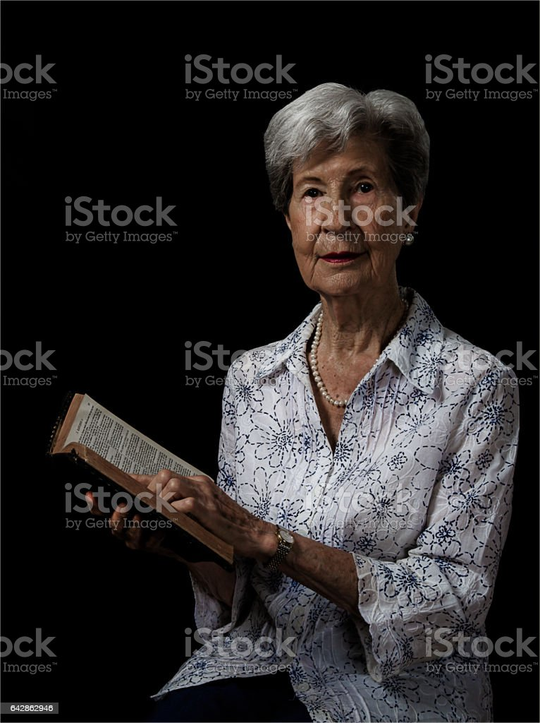 Senior Lady Looking Up from Reading Bible stock photo