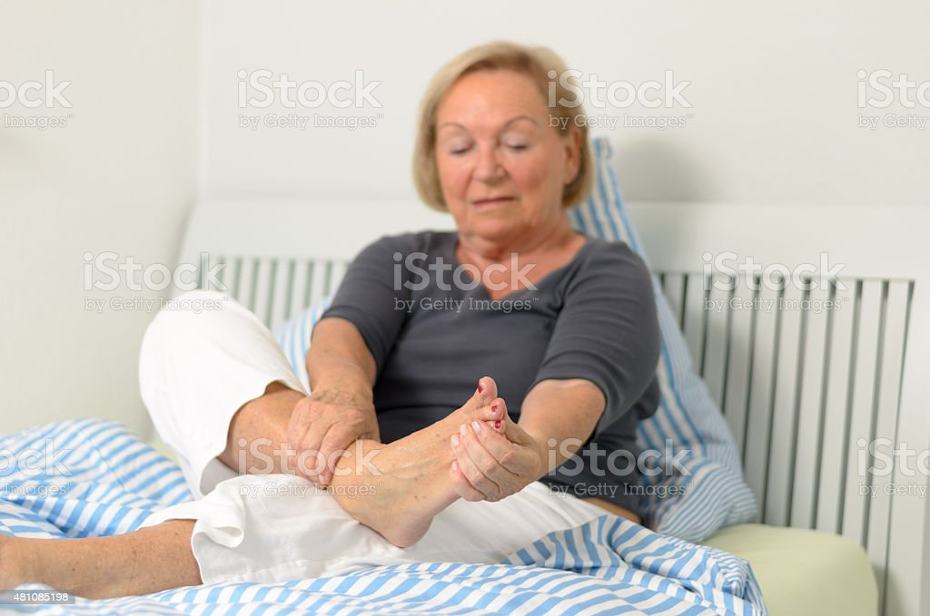 Senior lady massaging her foot stock photo