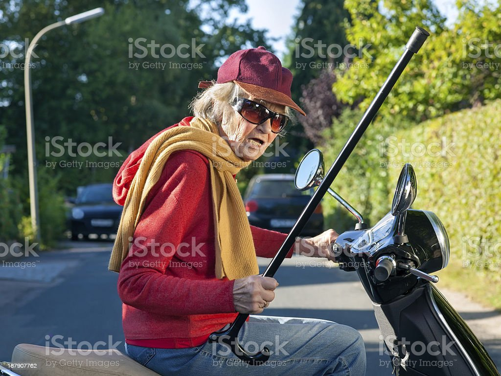 Senior lady on a scooter waving her cane. stock photo