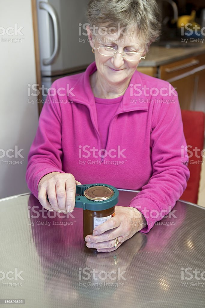 senior lady opening a jar in her kitchen stock photo