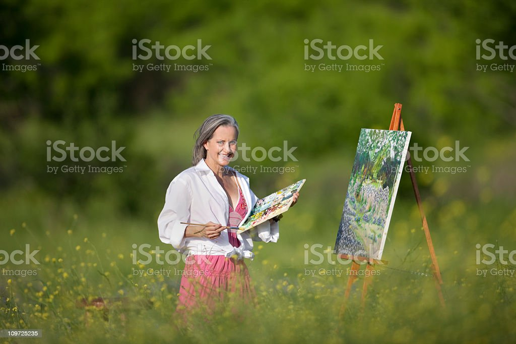Senior Lady Painting In Field Of Wildflowers royalty-free stock photo