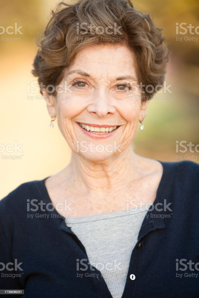 A senior lady smiling in a blue cardigan royalty-free stock photo