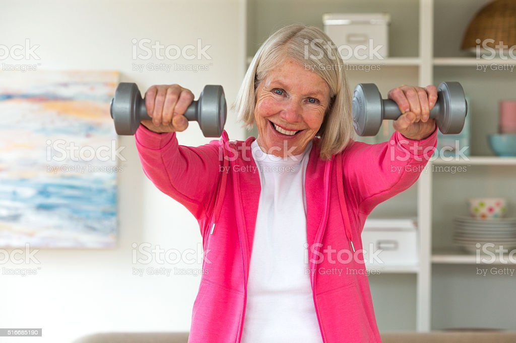 Senior lady using dumbbells. stock photo
