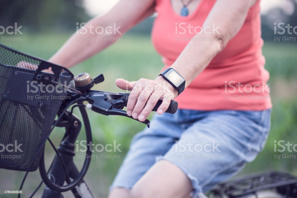 Senior lady using smart watch while cycling. stock photo