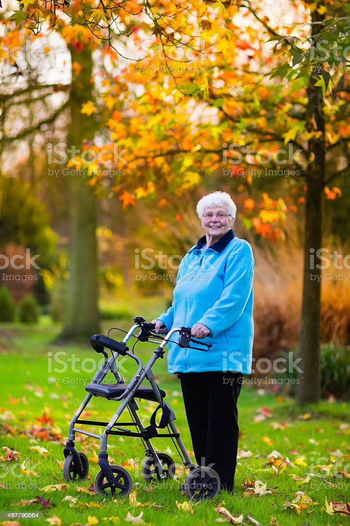 Senior lady with a walker in autumn park stock photo