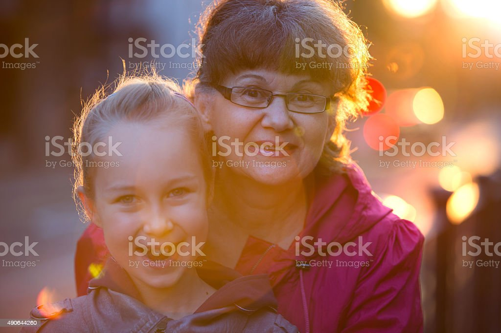 Senior lady with granddaughter hugging and smiling stock photo