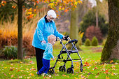 Senior lady with walker enjoying family visit walking with grandchild