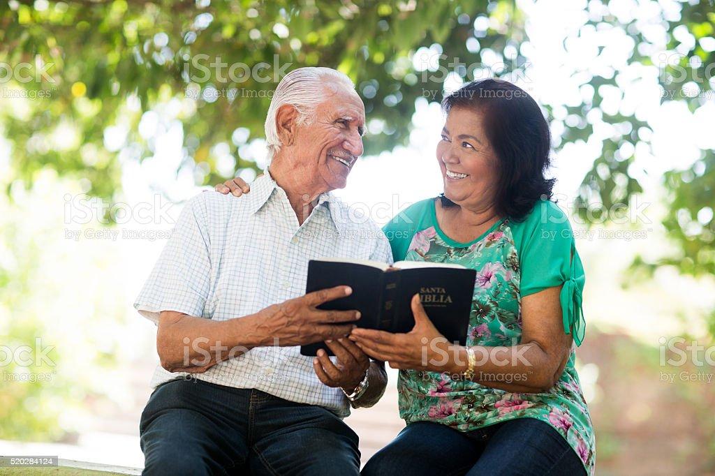 Senior latin couple holding Bible and smiling stock photo