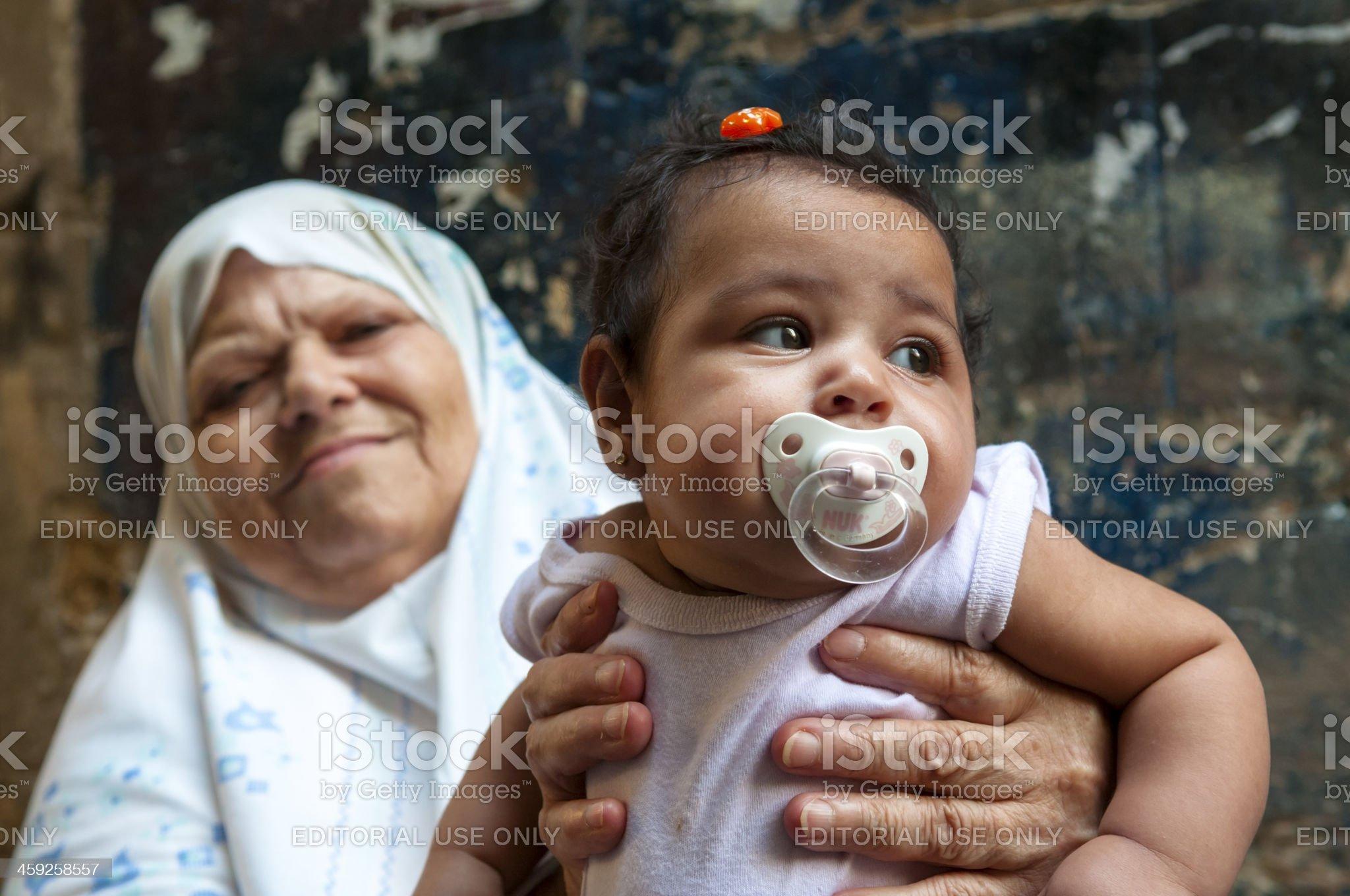 Senior Lebanese woman holding her grandchild in Sidon, Lebanon royalty-free stock photo