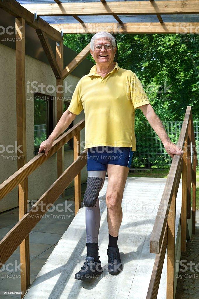 Senior leg amputee walking down ramp for exercise. stock photo