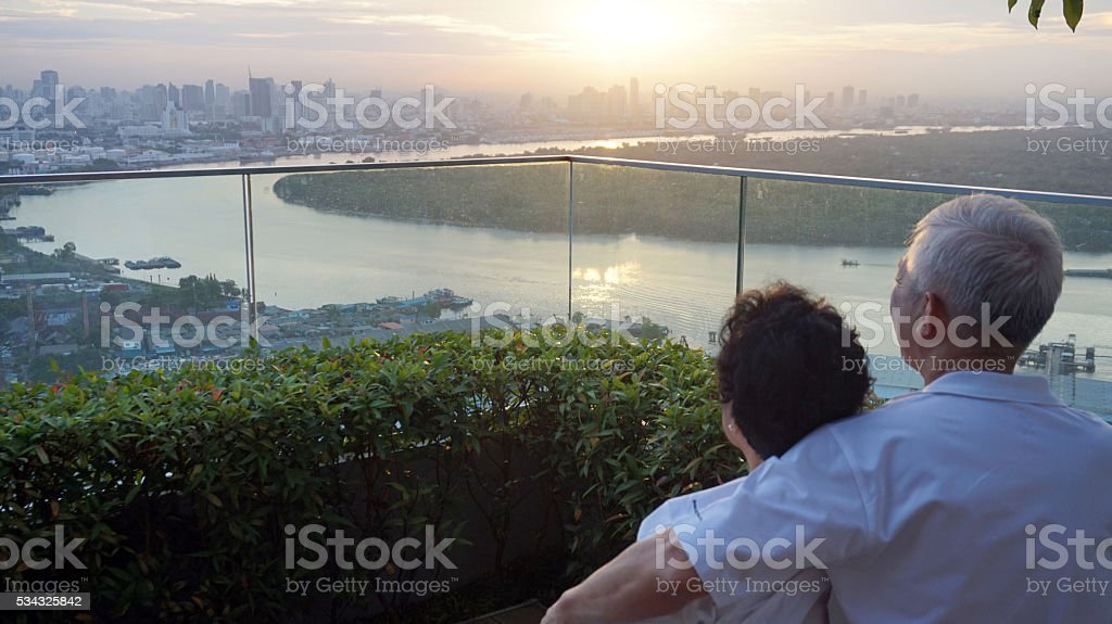 senior looking at sunrise together over city skyline stock photo