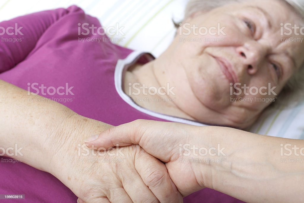 senior lying in bed and welcomes nurse royalty-free stock photo