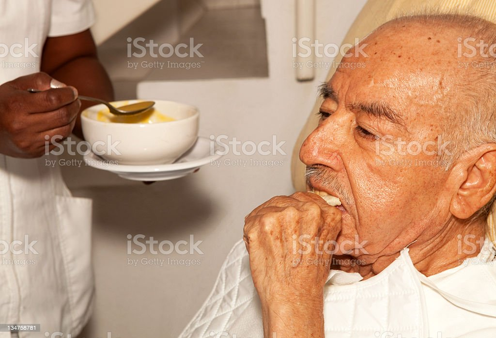 senior male being fed royalty-free stock photo