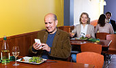 Senior male businessman with food and smartphone