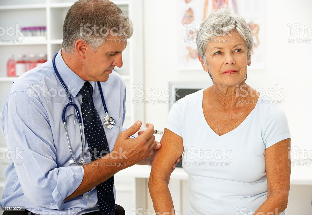 A senior male doctor injecting a senior female patient stock photo