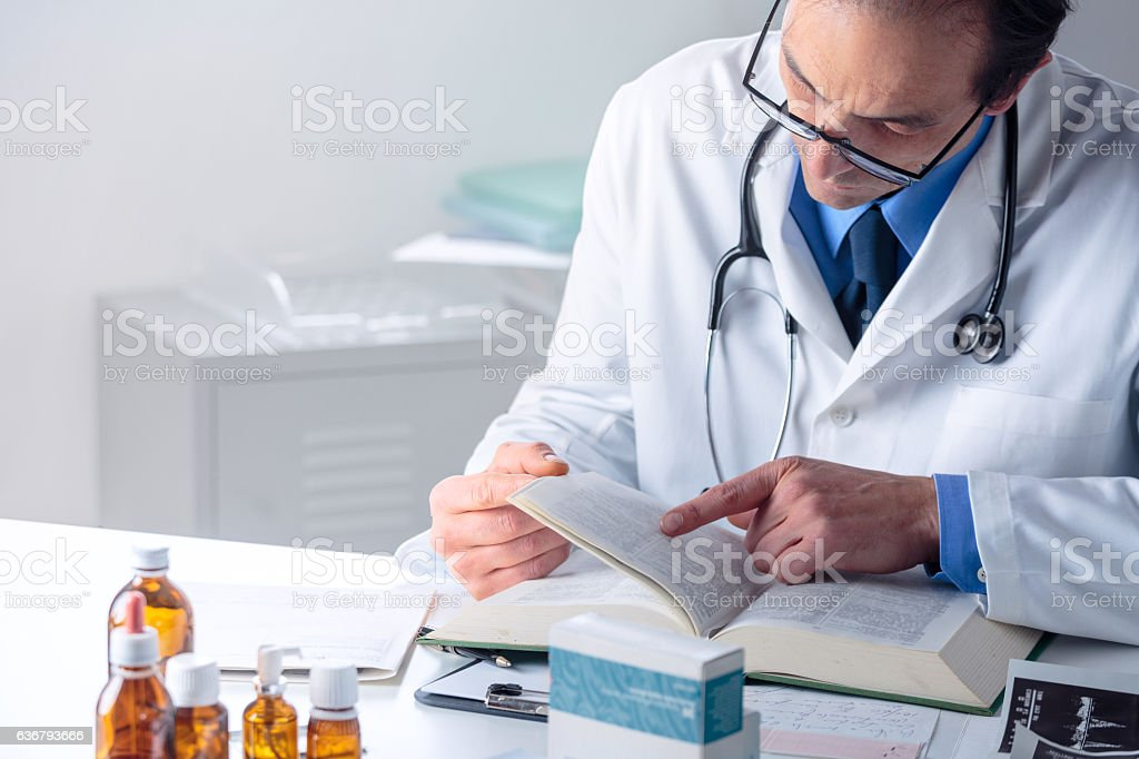 Senior Male Doctor looking for Information in a Medical Book stock photo
