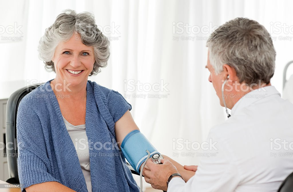 A senior male doctor taking the blood pressure of a woman royalty-free stock photo