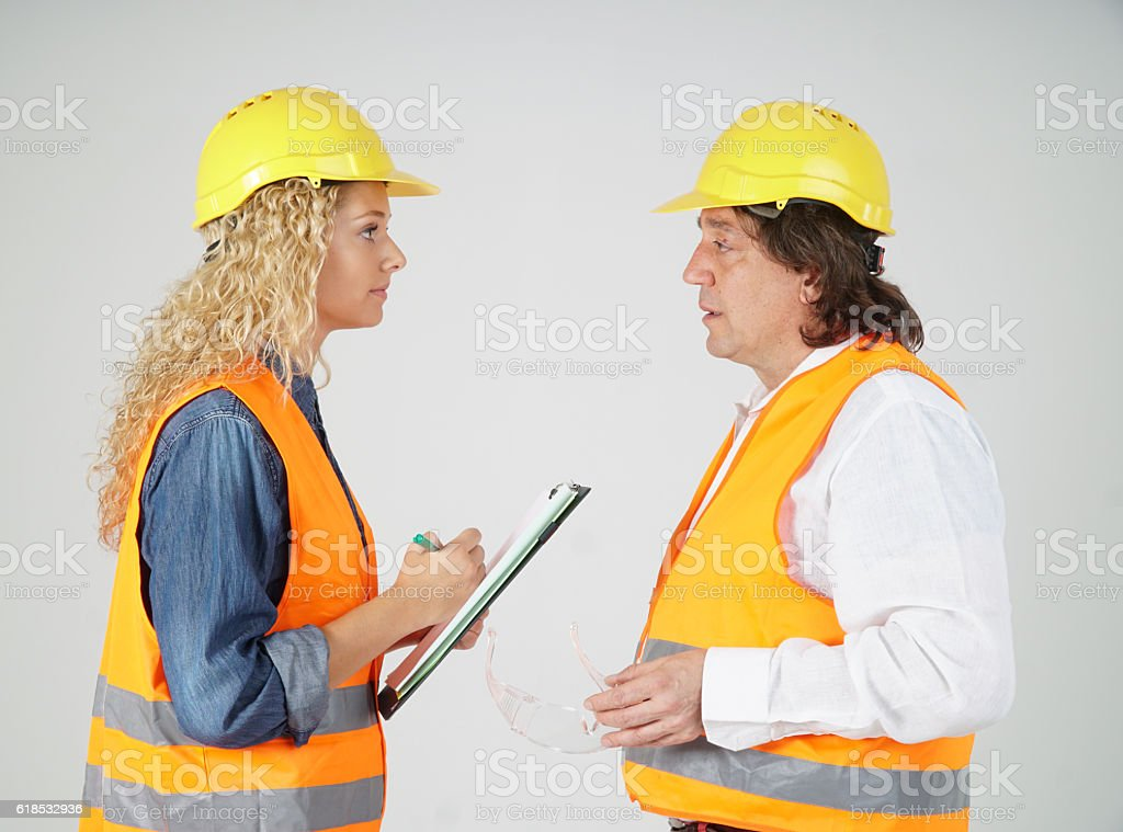 Senior male engineer and young female trainee, profile stock photo