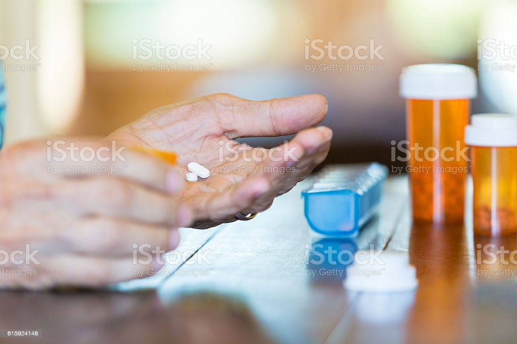 Senior male holding pills in his hand stock photo