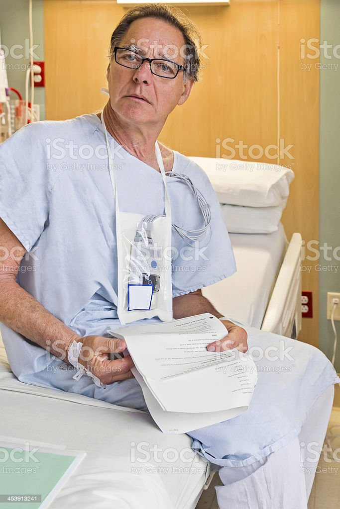 Senior male hospital patient holding his discharge instructions stock photo