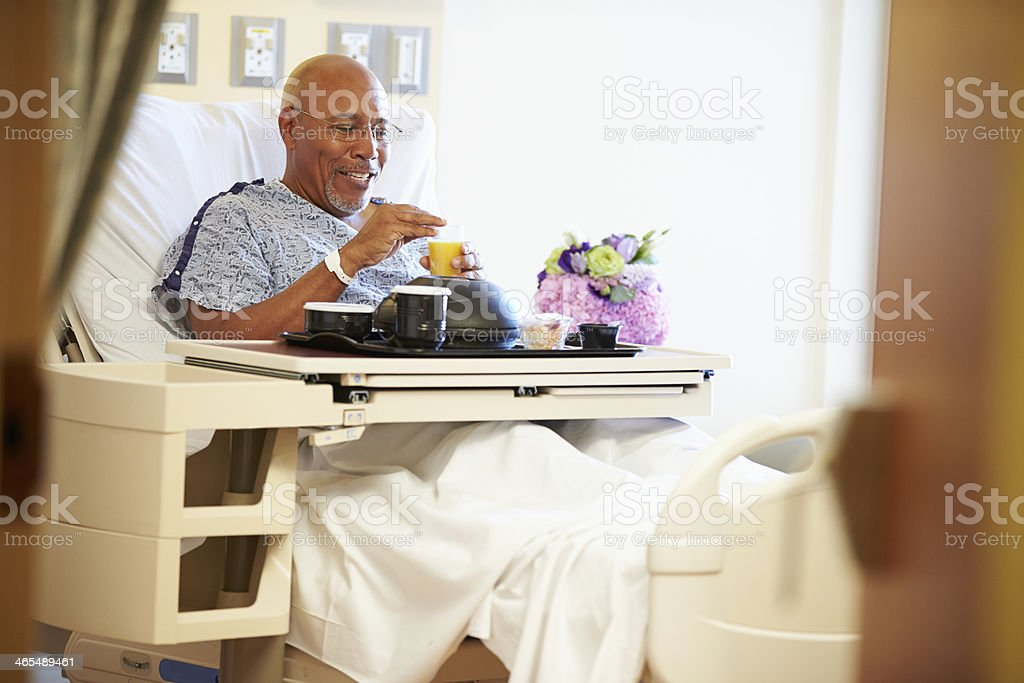 Senior Male Patient Enjoying Meal In Hospital Bed stock photo